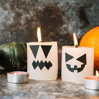 Burning candles in Halloween style standing with pumpkins on background