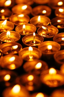 Burning candles. Many yellow candles glow in dark. Closeup