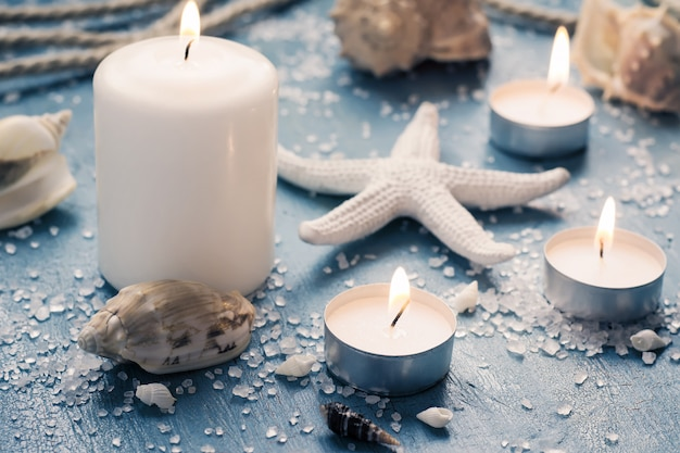 Burning candles on marine items, monochrome toning in blue and white colors