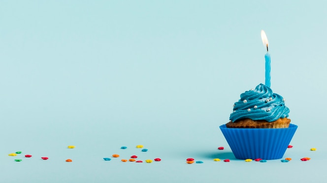Burning candles on muffins with star sprinkles against blue backdrop