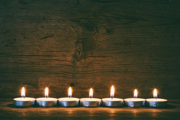 Горящие свечи на старых досках сарая