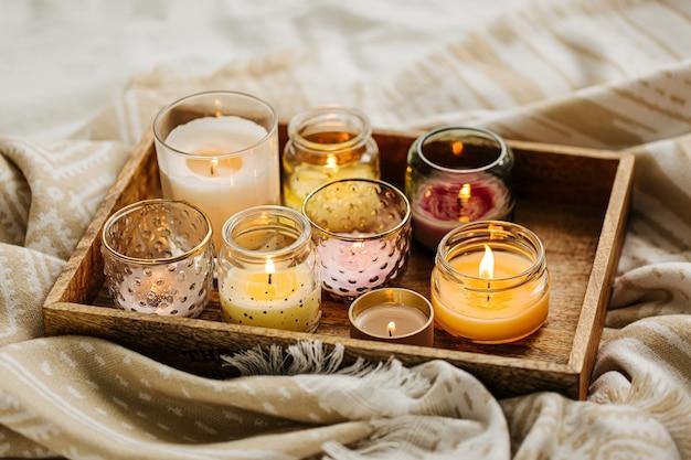 Горящие свечи на деревянном подносе с теплым пледом в постели. скандинавский стиль. концепция hygge.