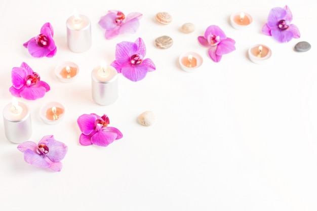 Burning candles and orchid flowers on wooden background. relaxation spa concept