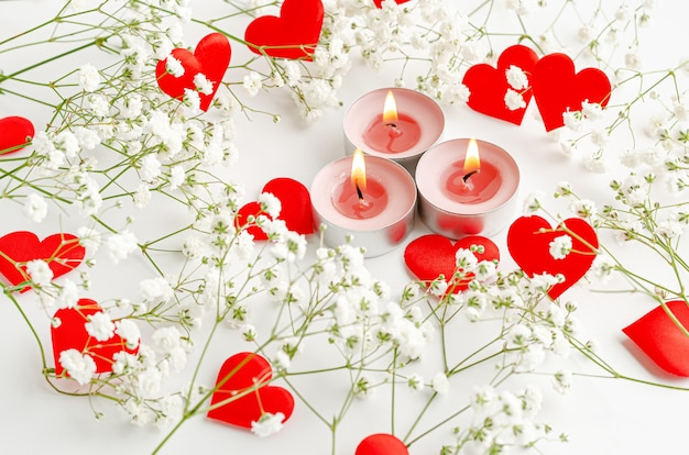 Burning candles and red hearts decorated with flowers