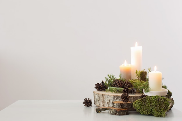 Burning candles on saw with cones and branches on white backgrou