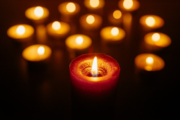 Burning candles. shallow depth of field. many candles burning at night. many candle flames glowing.