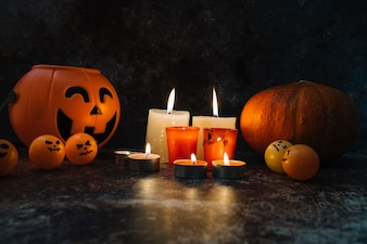 Burning candles standing among orange basket and pumpkin and pictured balls