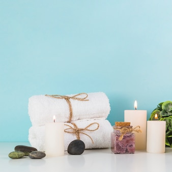 Burning candles; towels; spa stones; scrub bottles in front of blue wall