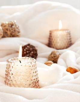 Burning candles on white fabric