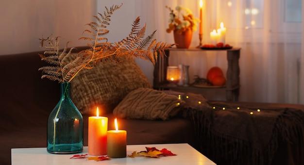 집에 있는 흰색 테이블에 가을 장식으로 촛불을 태우다