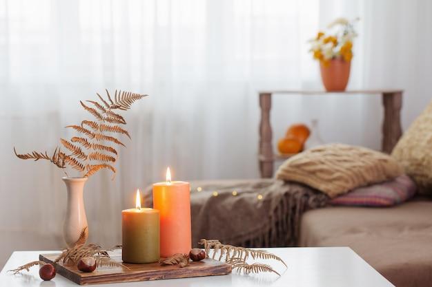 Горящие свечи с осенним декором на белом столе дома