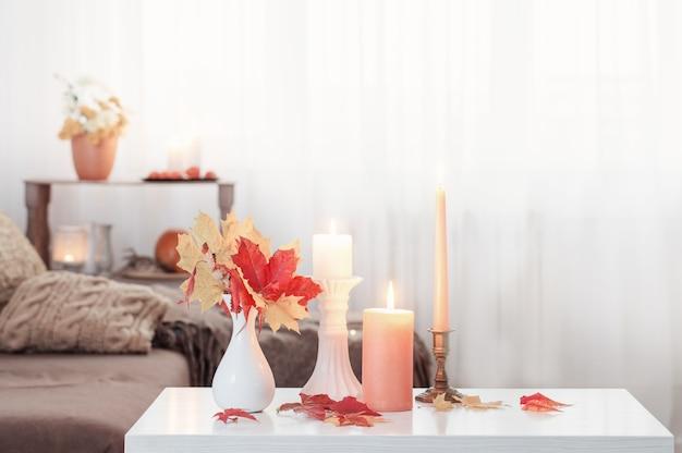 自宅の白いテーブルに秋の装飾が施されたキャンドルを燃やす