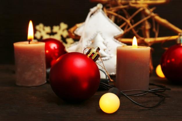 Горящие свечи с рождественскими аксессуарами на деревянном столе