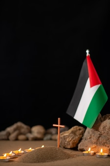 Burning candles with palestinian flag around little grave