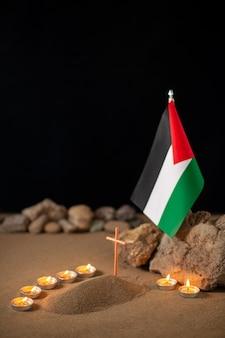 Горящие свечи с палестинским флагом вокруг маленькой могилы