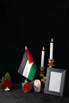 Горящие свечи с палестинским флагом на темной поверхности