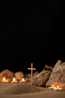 Горящие свечи с камнями вокруг маленькой могилы как похороны в память о смерти