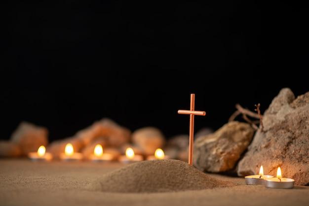 Candele accese con pietre intorno alla piccola tomba come funerale di morte in memoria
