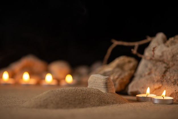 Burning candles with stones around little grave as memory funeral death