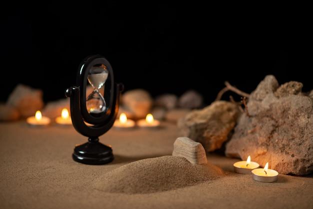 Горящие свечи с камнями вокруг маленькой могилы в память о похоронах