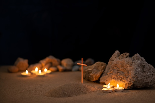 Burning candles with stones and little grave on sand as memory death funeral