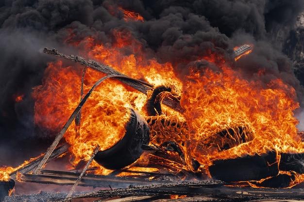 燃える車の車輪、赤オレンジ色の火の強い炎、空の黒い煙の雲。セレクティブフォーカス、強い火からぼかす。