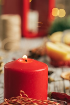 Burning christmas candle close up on wooden table