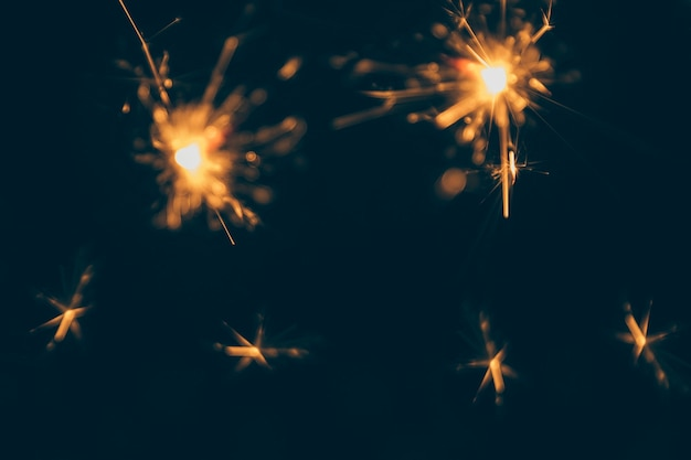 Burning christmas sparklers isolated on dark backdrop