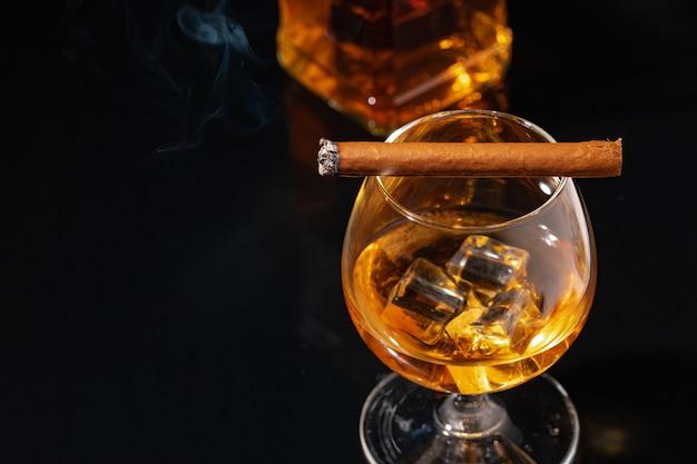 Горящая сигара и стакан виски на черном крупным планом