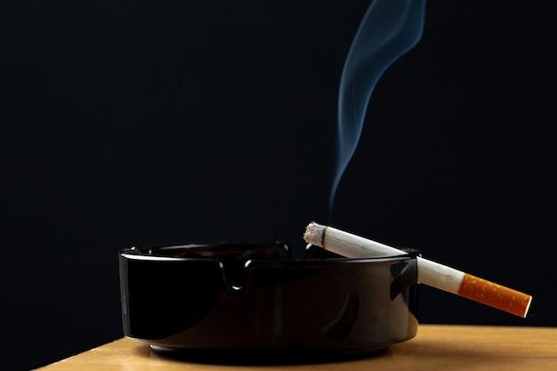 Горящая сигарета в черной пепельнице крупным планом
