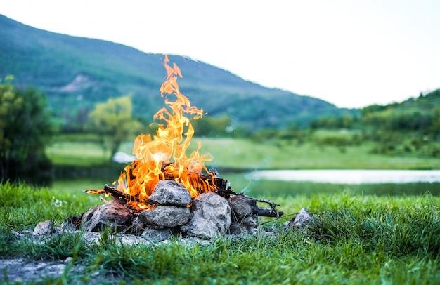 たき火で石炭を燃焼します。湖の背景に自然の中で燃える火火の残り火。
