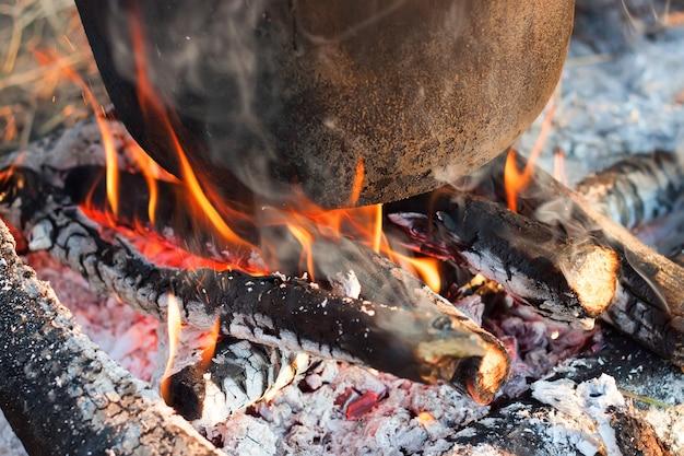 불타는 석탄과 관광 냄비 바닥. 사진을 닫습니다.