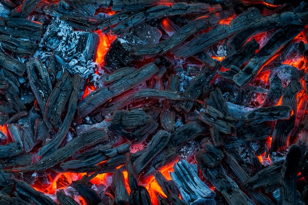 Burning coals, charcoal. charcoal in the background.