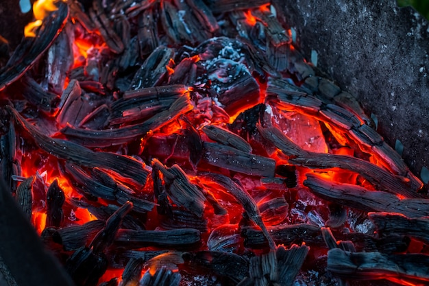 Burning coals. decaying charcoal. texture embers closeup. burning charcoal in the background.