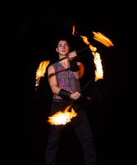 Burning energy. handsome man juggle flaming batons. fire juggling. fire energy. energetic twirling. flame and sparks. night performance. amusement show. light up and juggle.