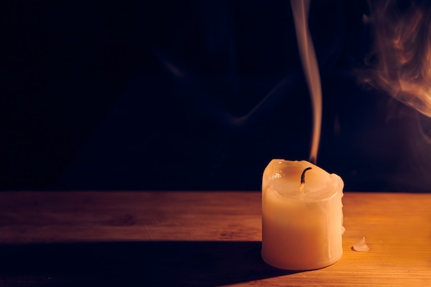 Burning and extinguished candle on wooden table. smooth, white smoke from candle. flame of the hope and memory. standing out from crowd, exhausting or dying concept. close up view with copy space.