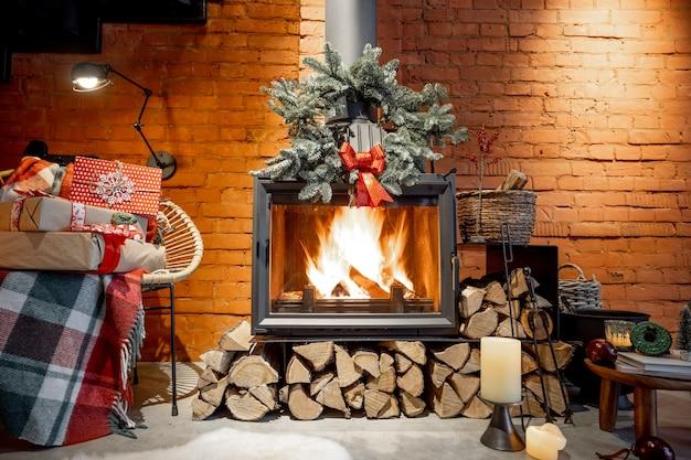 Горящий камин, украшенный подарками и новогодним венком в уютном домашнем интерьере.
