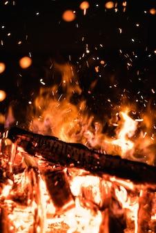 Горящие дрова в костре с искрами в темноте ярко-оранжевое пламя