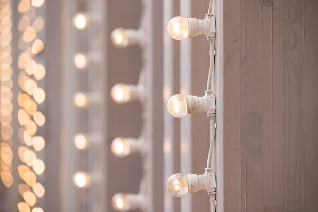 A burning garland of light bulbs on a vertical surface for a holiday party or wedding