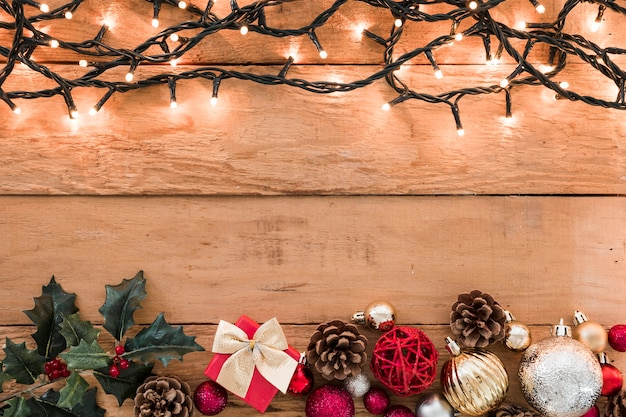 Burning garland with baubles on table