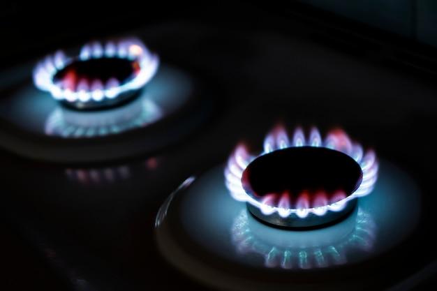 Горящая газовая горелка в темноте. пламя горящего газового огня на черном фоне.