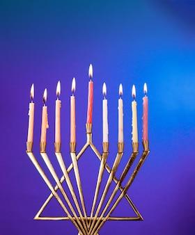 Burning hanukkah candles in a menorah on blue background