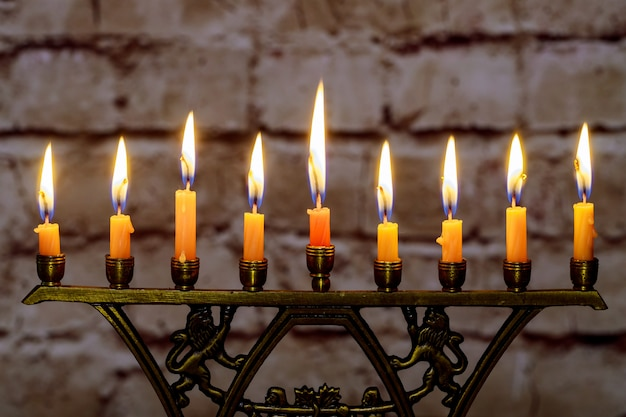 Burning hanukkah candles in a menorah on colorful candles from a menorah