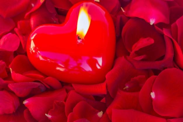 赤いバラの花びらで燃えるハートキャンドル