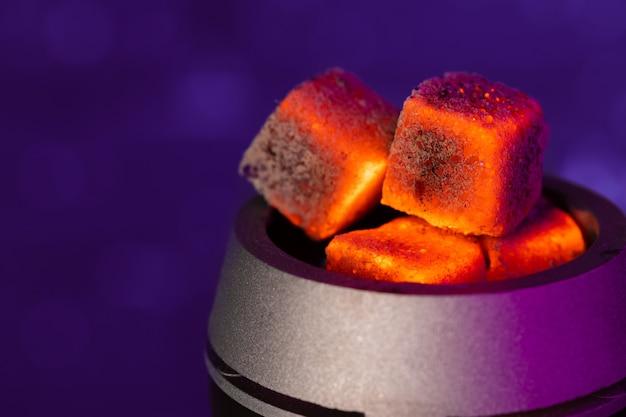 Burning hookah coals in hookah bowl close up photo