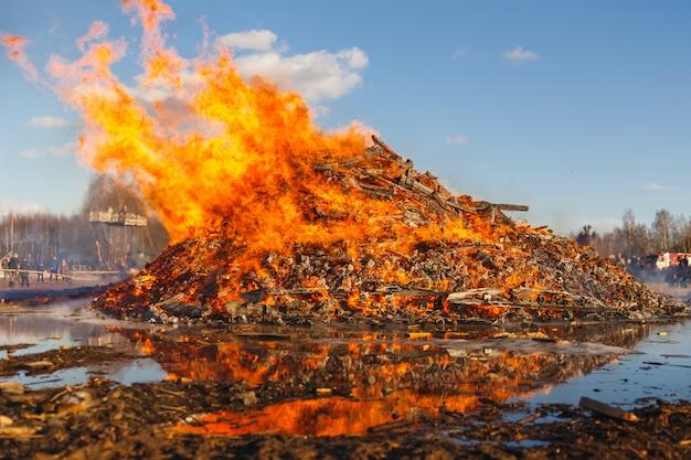 Burning huge bonfire against the blue sky.
