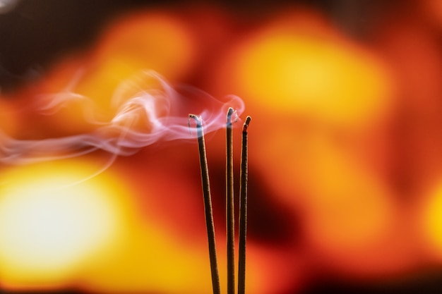 Burning incense sticks with smoke, joss sticks burning at a vintage buddhist temple