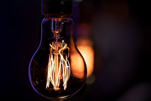A burning lamp hangs in the dark. the concept of decor and atmosphere.