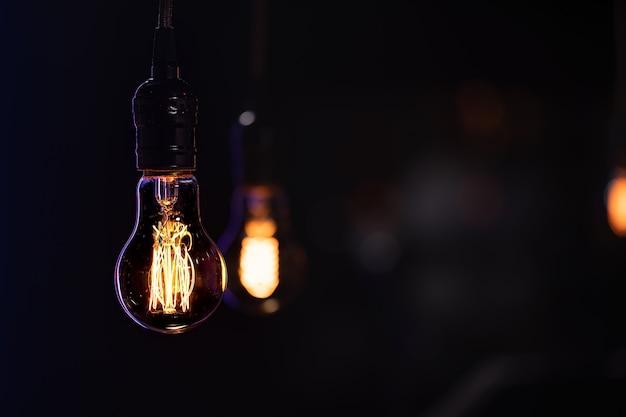 A burning lamp hangs in the dark