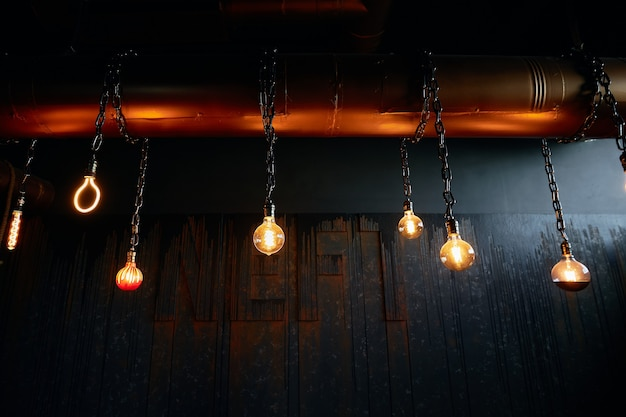 Burning lamps of different sizes hang on chains in a row